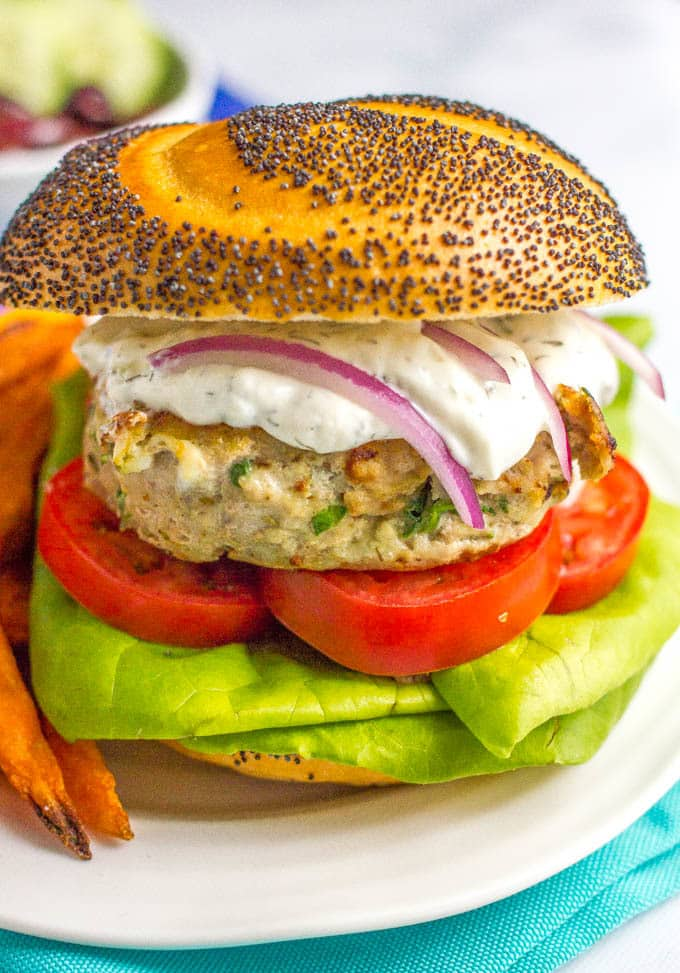 Greek turkey burgers with tzatziki sauce are loaded with spinach, red onion and feta cheese for a delicious but easy taste of Greece! | www.familyfoodonthetable.com