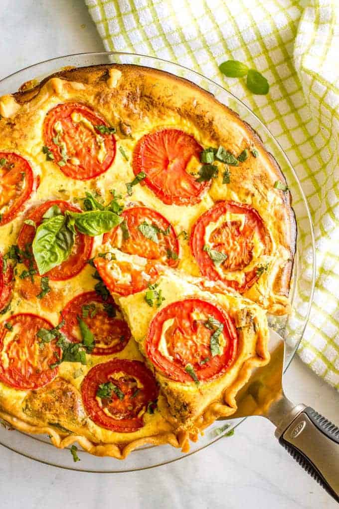 This easy tomato breakfast tart with basil + two cheeses has sliced tomatoes on top for a unique and beautiful brunch presentation - a great recipe for company (and Mother's Day!) #tomatoes #breakfasttart #brunchrecipes #brunch