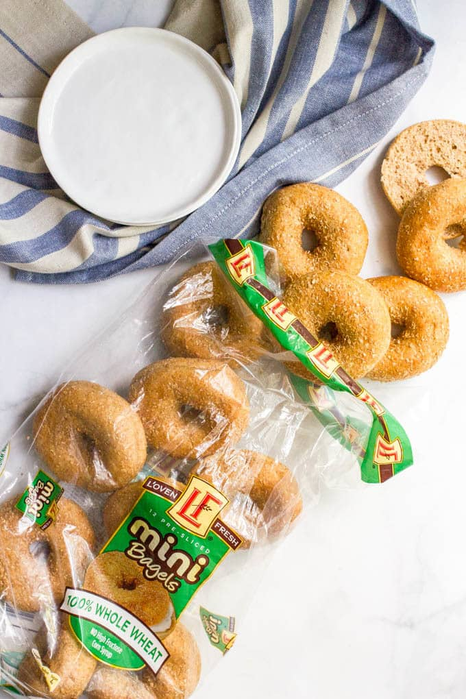 A bag of mini bagels spilling out on a white counter with a stack of plates nearby