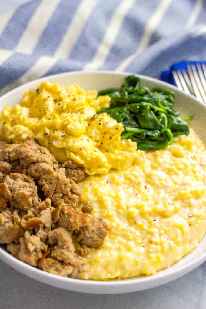 A large white breakfast bowl filled with cheesy grits with crumbled sausage, scrambled eggs and sautéed spinach on top