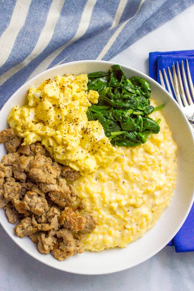A white bowl filled with cheesy grits topped with crumbled sausage, scrambled eggs and sautéed spinach
