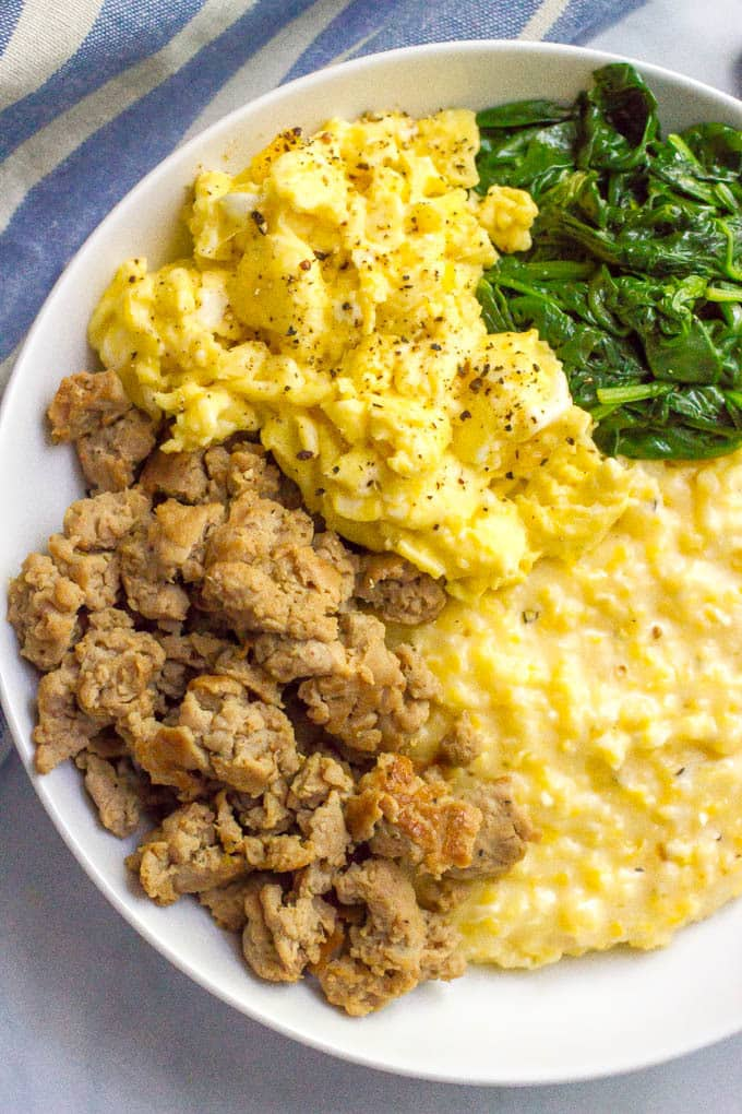 A breakfast bowl of cheesy grits with crumbled sausage, scrambled eggs and sautéed spinach
