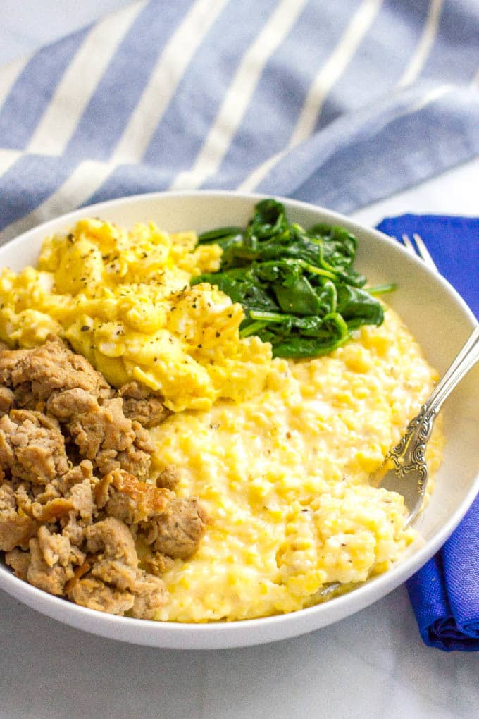 A fork resting in a bowl of cheesy grits with crumbled sausage, scrambled eggs and sautéed spinach