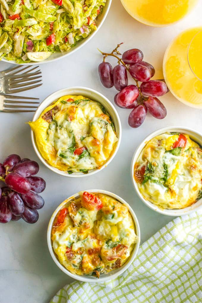 Individual egg breakfast ramekins set out with orange juice and fruit