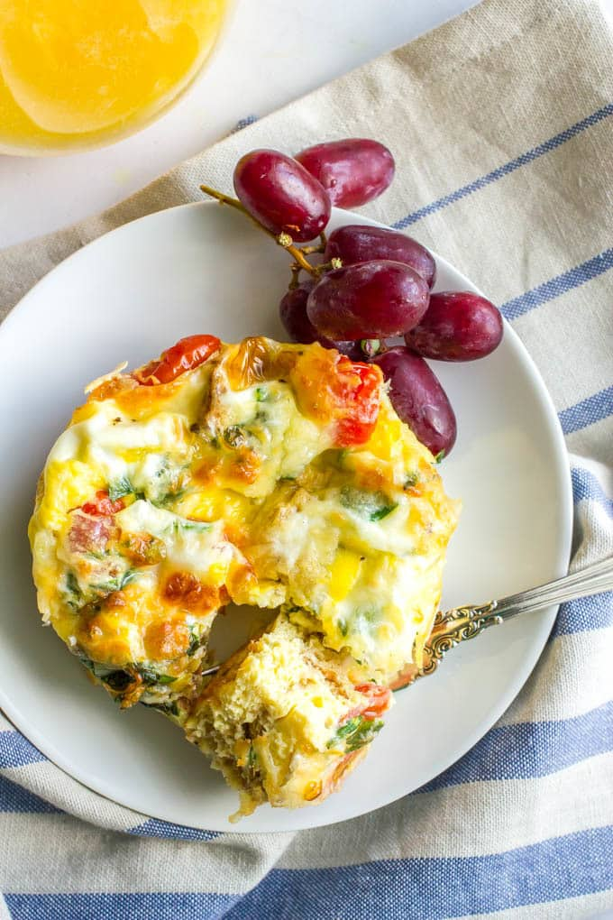 Individual egg breakfast casserole with veggies served on a white plate with grapes