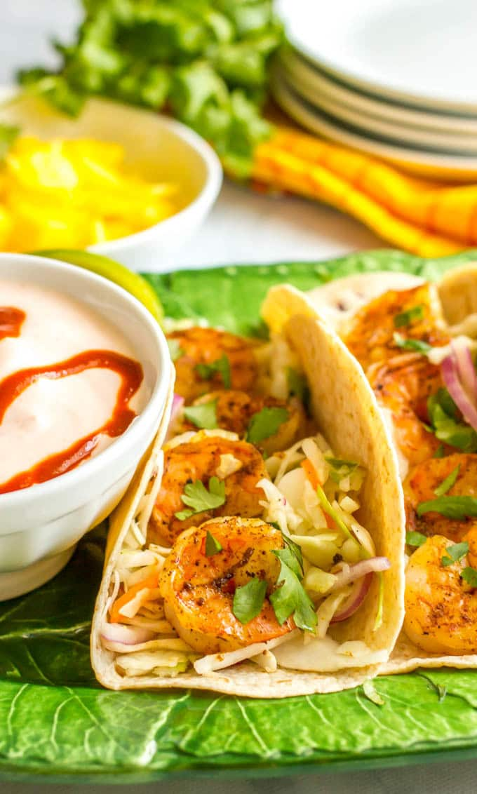 Shrimp tacos with lime cabbage slaw and spicy yogurt sauce make for a quick and easy dinner that's big on flavor!   www.familyfoodonthetable.com