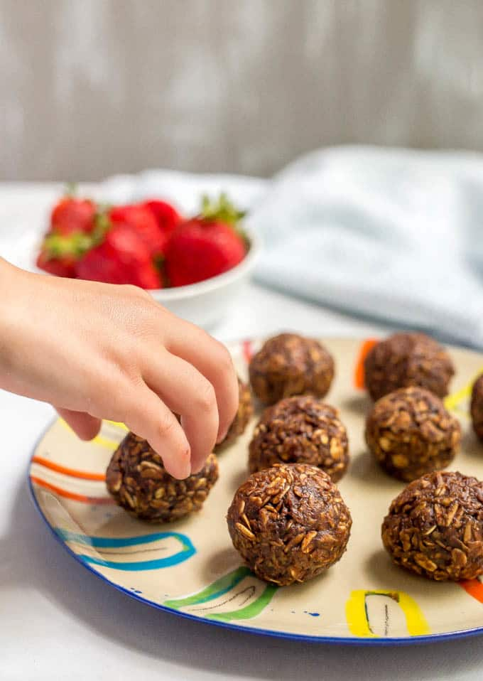Chocolate cookie balls with hand reaching for one