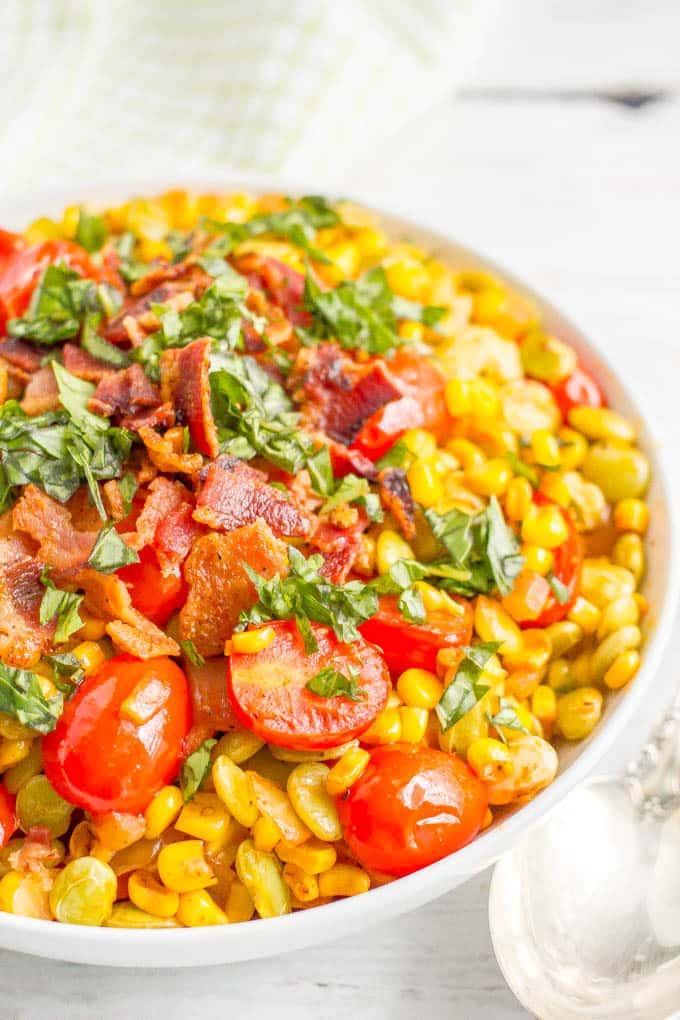 A large white serving bowl of succotash with bacon and fresh herbs