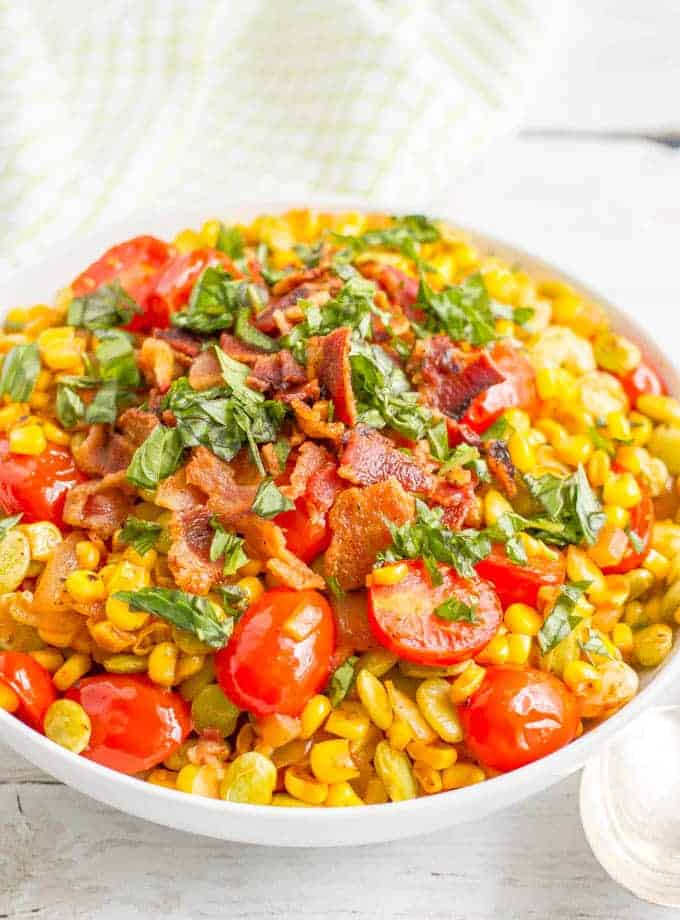 Easy succotash recipe with corn, lime beans, tomatoes and bacon in a large white serving bowl