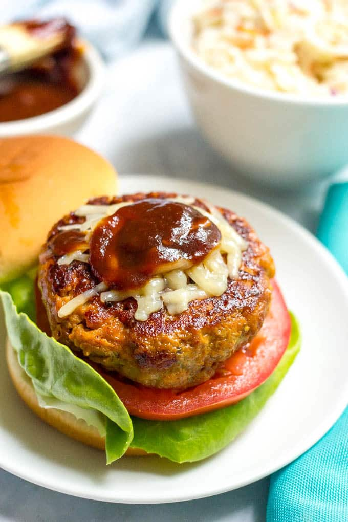 BBQ chicken burger plated with cheese and BBQ sauce on top