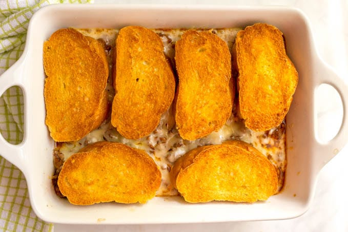 Cheesy sloppy Joe casserole after baking with crusty, golden brown bread