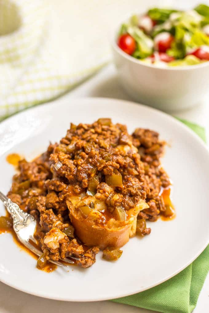 Cheesy sloppy Joe casserole served on plate with a side salad in a bowl in background
