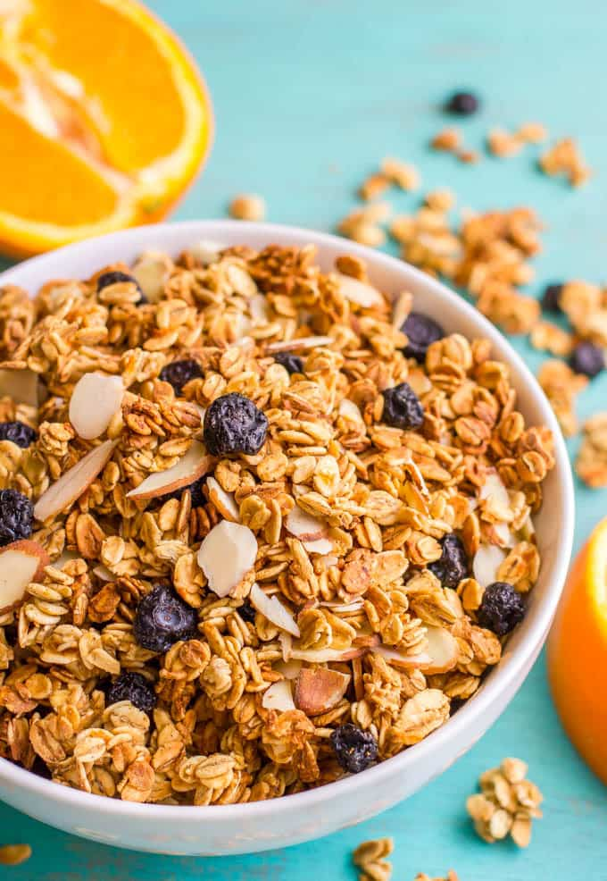A bowl full of granola with blueberries and almonds and oranges nearby