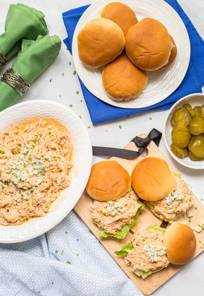 A tailgating spread of crock pot buffalo chicken with sliders and fixings