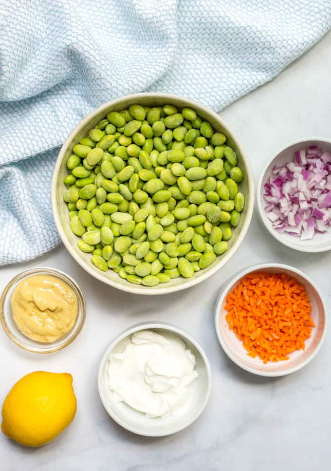 Ingredients in white bowls to make smashed edamame salad