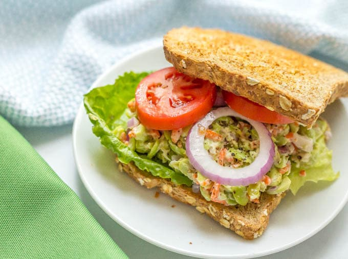 Smashed edamame salad sandwich with tomatoes and red onion
