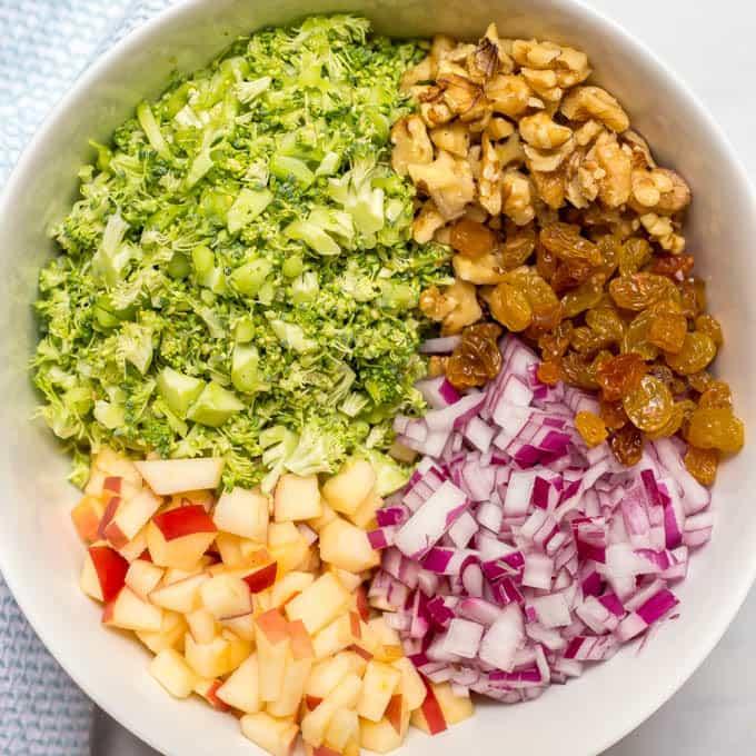Healthy broccoli apple salad ingredients arranged in bowl