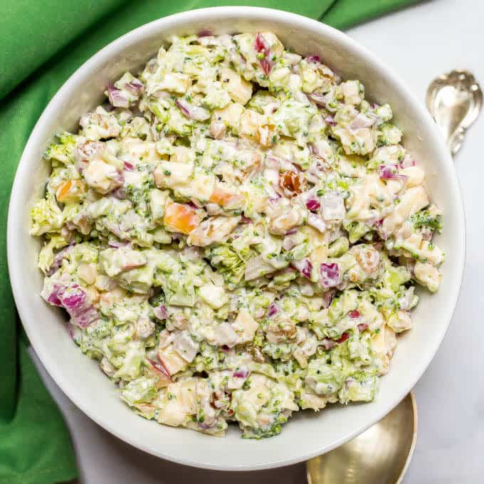 Healthy broccoli apple salad with dressing mixed in white bowl