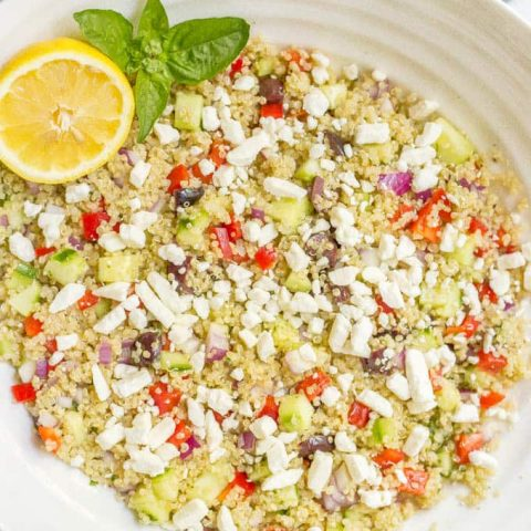 Mediterranean quinoa salad mixed in bowl and topped with feta cheese