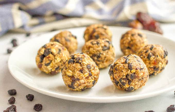 No bake blueberry oatmeal cookie balls on plate with scattered dried blueberries