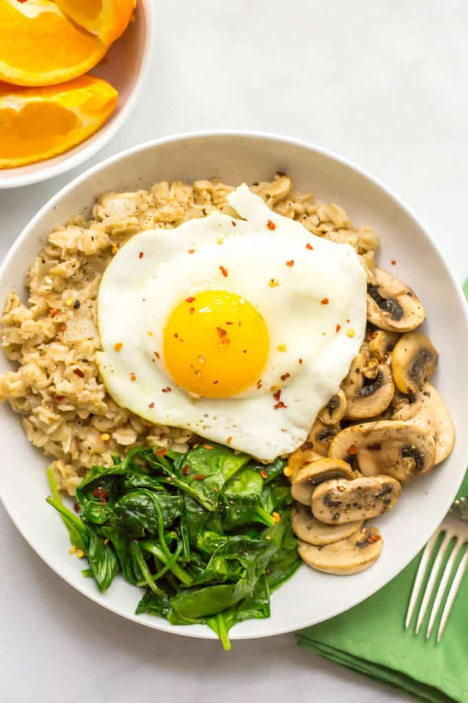 Savory oatmeal bowl with sauteed mushrooms, spinach and a fried egg on top in a bowl with oranges on side