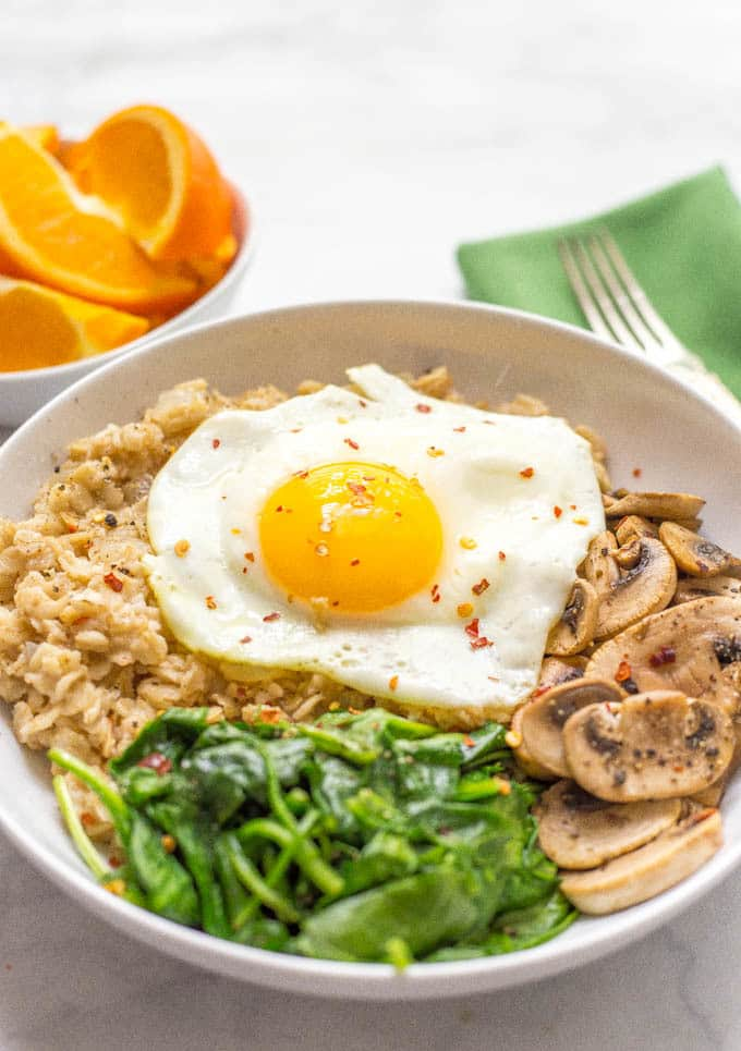 Savory oatmeal bowl with sauteed mushrooms, spinach and a fried egg on top in a bowl with red pepper flakes on top