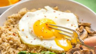 Savory oatmeal bowl with mushrooms, spinach and fried egg