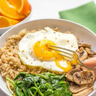 A savory oatmeal bowl with sautéed mushrooms and spinach, topped with a fried egg for an easy but rich and luxurious breakfast!