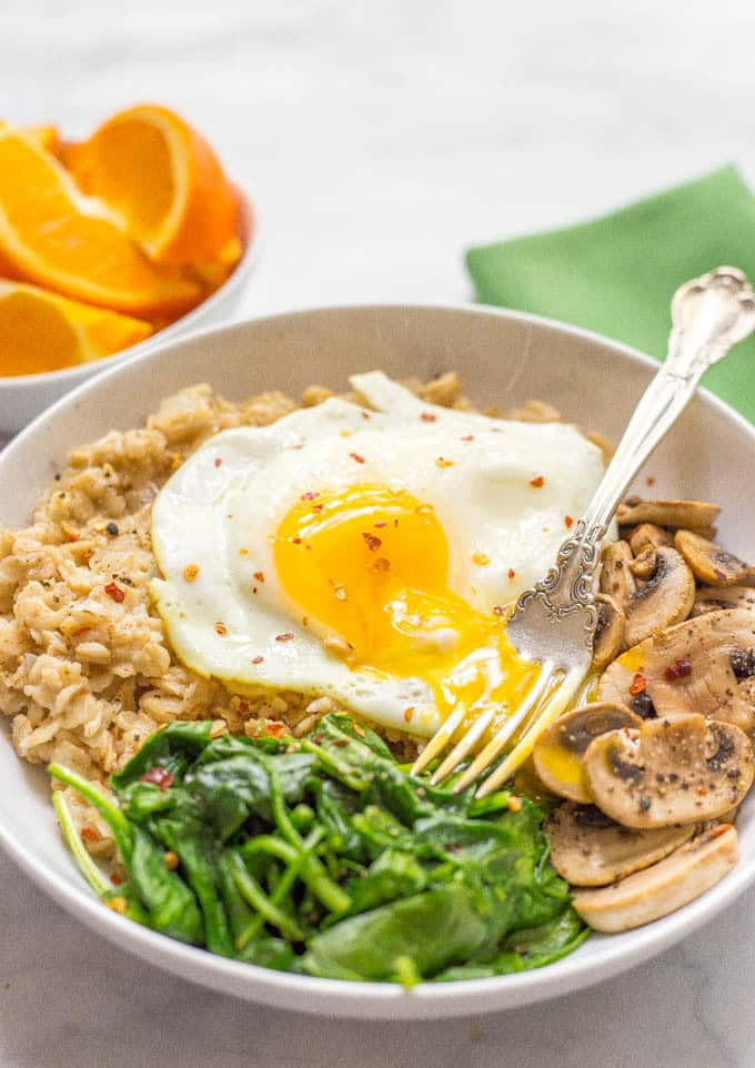 Savory oatmeal bowl with sauteed mushrooms, spinach and a fried egg on top in a bowl with fork sitting in egg yolk
