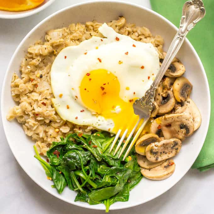 Savory oatmeal bowl with sauteed mushrooms, spinach and a fried egg on top in a bowl overhead shot with fork in runny egg yolk