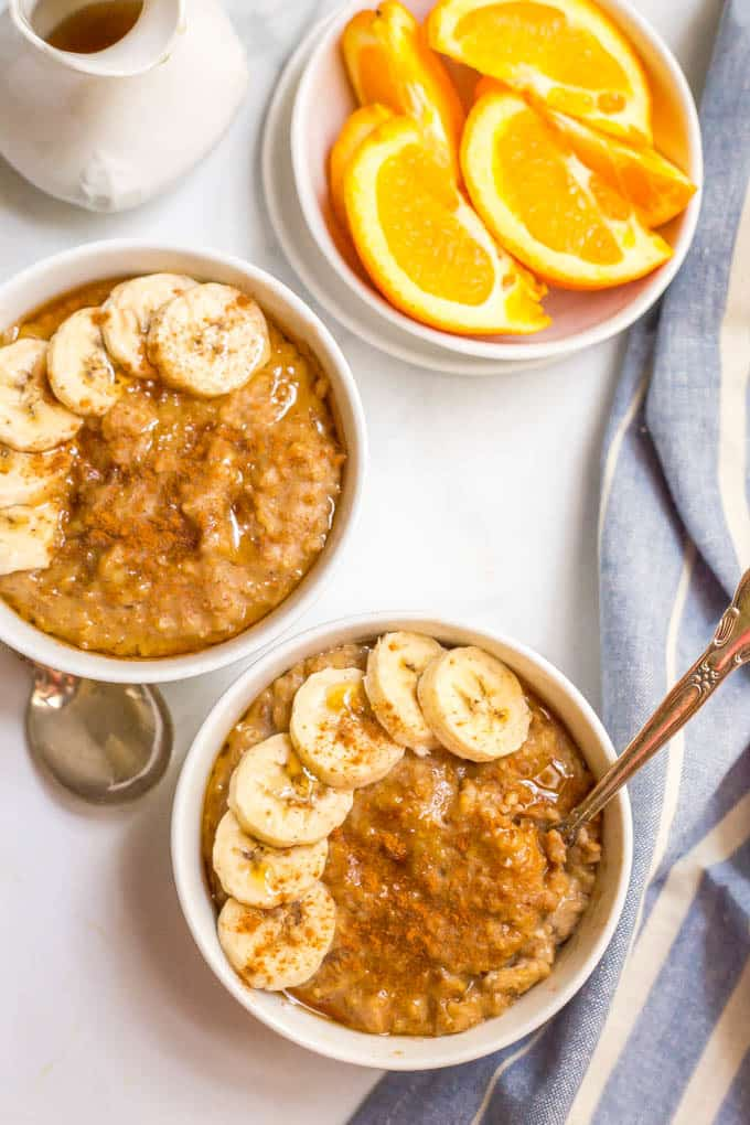 Slow cooker maple cinnamon oatmeal in bowls with sliced bananas and a side of oranges