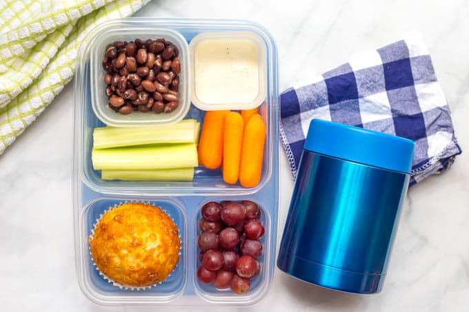 Easy cheesy cornbread muffin packed in compartment lunch box alongside a blue thermos
