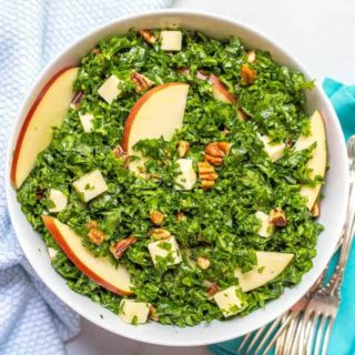 Kale apple salad with cheddar and pecans mixed in bowl