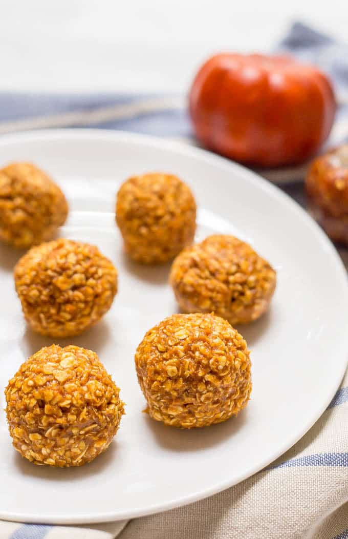 No-bake pumpkin protein energy balls close-up shot on a white plate with a blue linen underneath