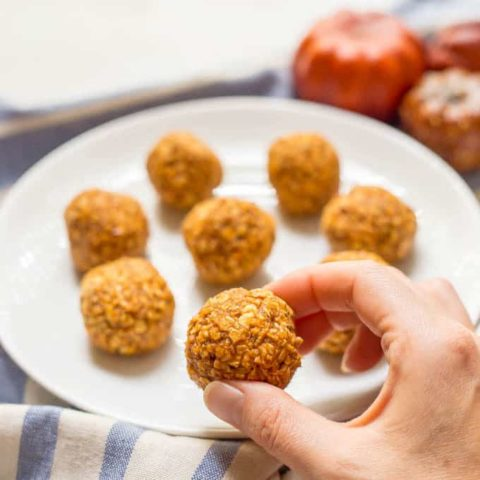 No-bake pumpkin protein energy balls on a plate with one held in hand