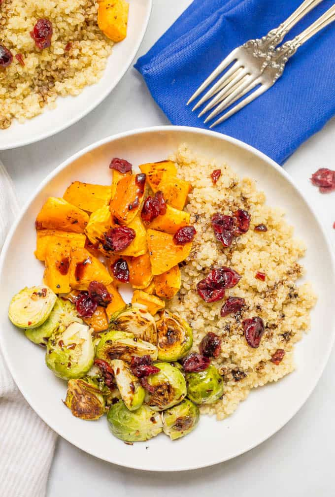 This quinoa bowl with butternut squash and Brussels sprouts is a filling vegetarian dinner that's topped with dried cranberries and balsamic vinegar for a warm, hearty bowl of delicious! | www.familyfoodonthetable.com