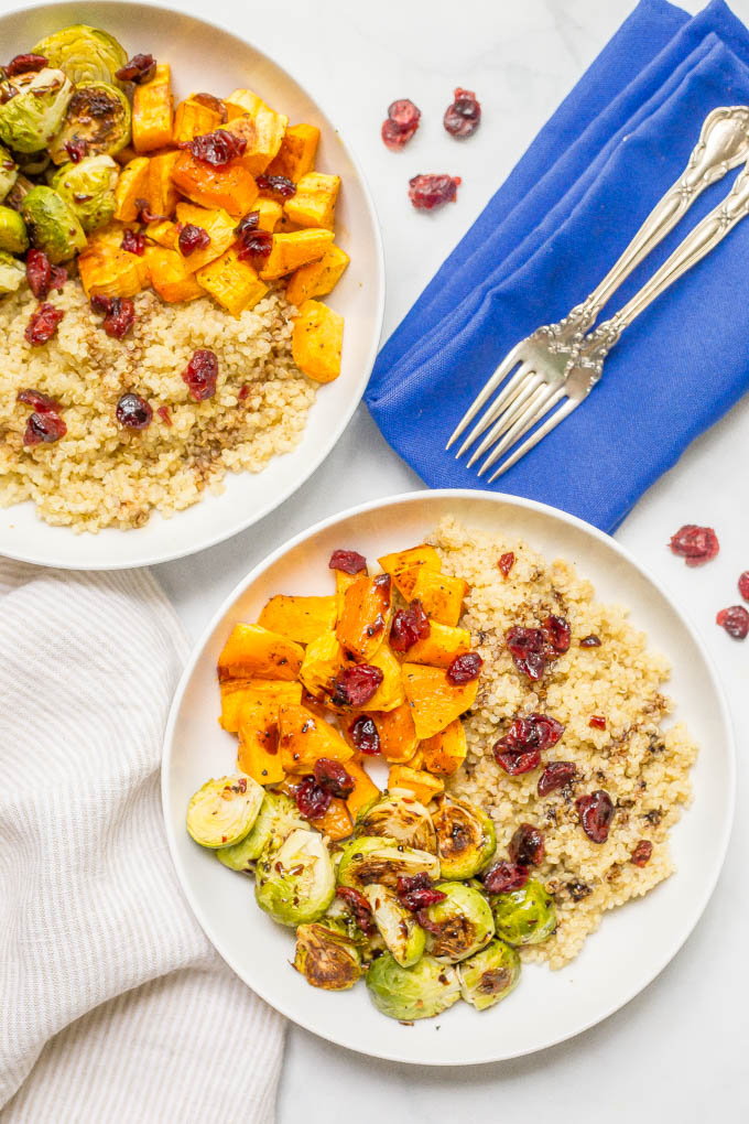Quinoa bowl with butternut squash and Brussels sprouts served in two bowls with dried cranberries on top and forks nearby