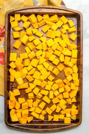 Cubed chunks of butternut squash on roasting pan