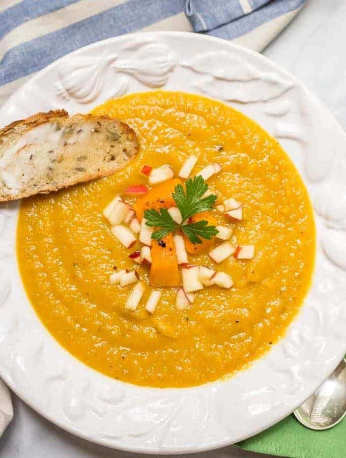Roasted butternut squash apple soup is perfect for a cozy fall dinner! This soup is thick and filling and has a perfect background of sweetness and warm spices!   www.familyfoodonthetable.com