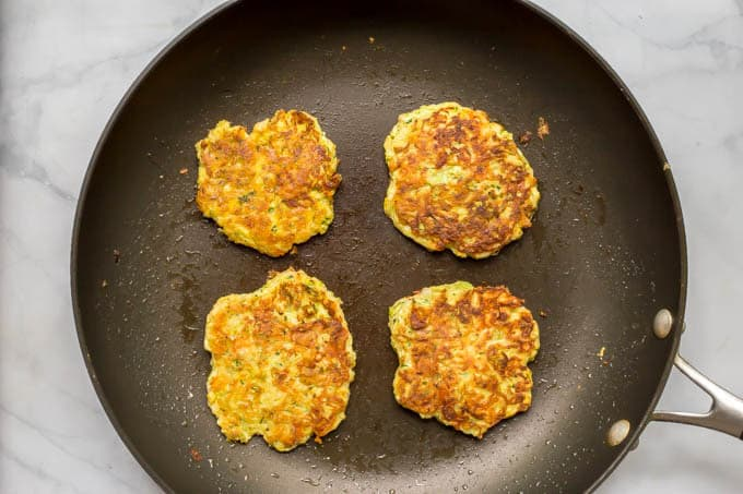 Whole wheat veggie pancakes being cooked in pan