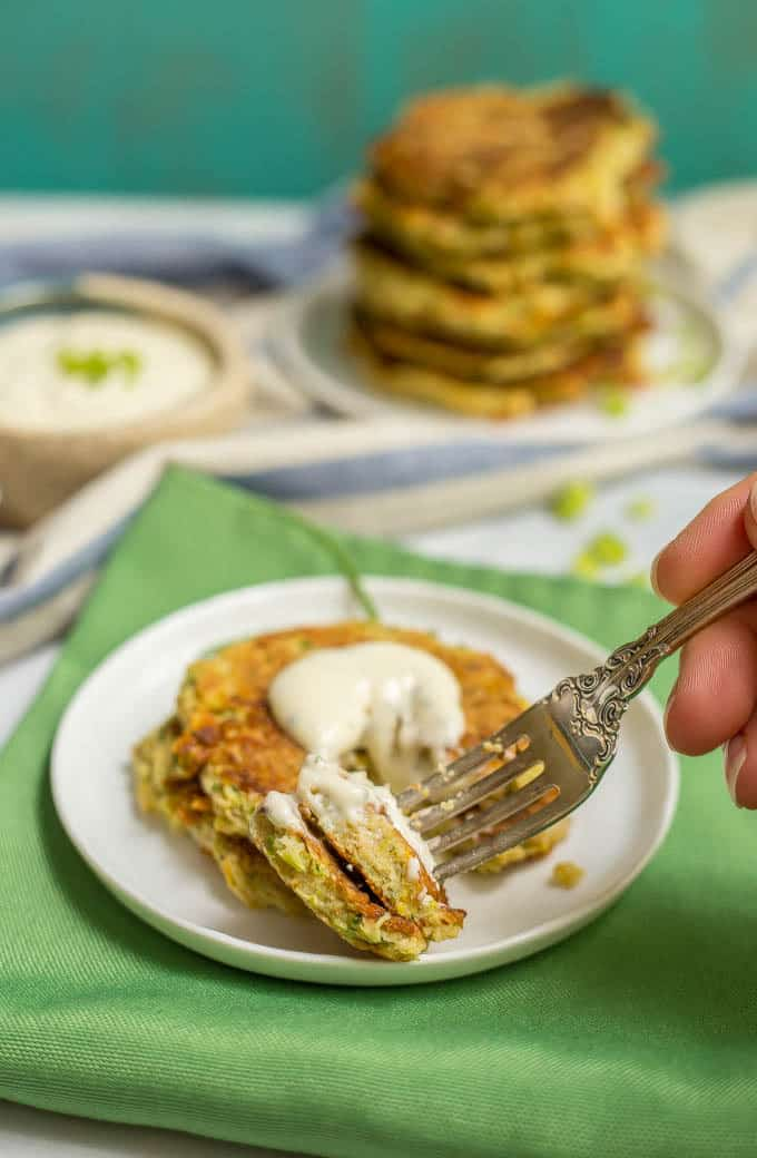 Whole wheat veggie pancakes with Ranch dressing and a forkful being taken out