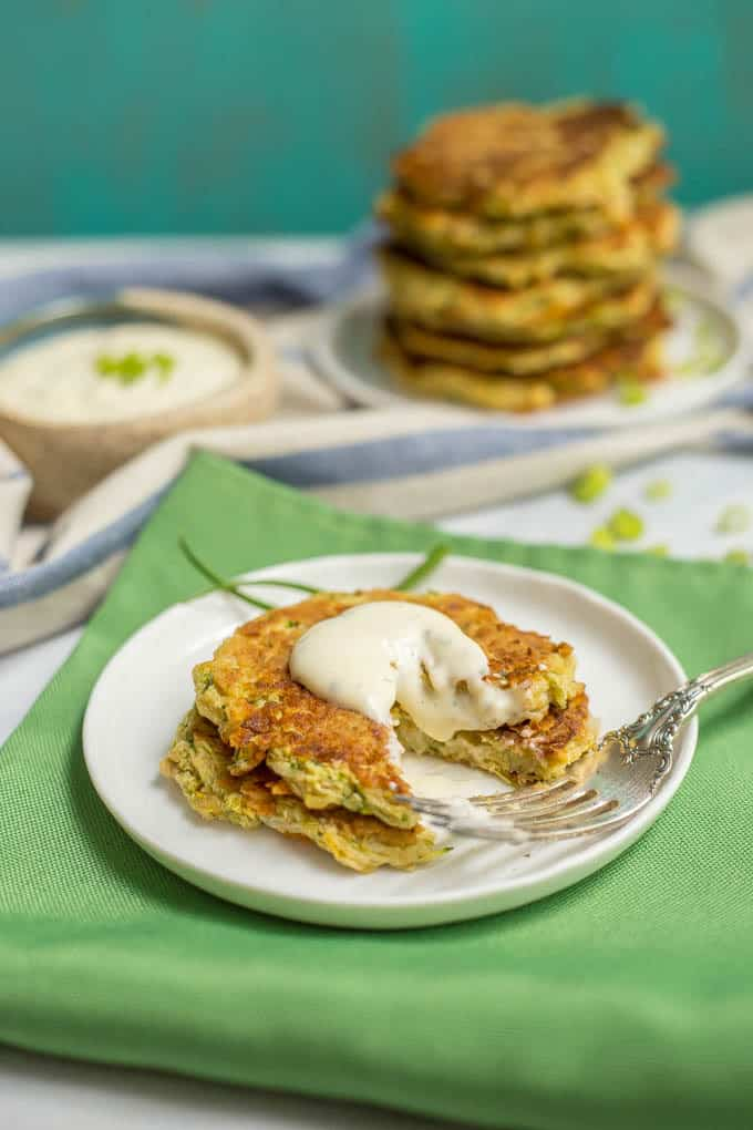 Plate of whole wheat veggie pancakes topped with Ranch dressing and a bite missing