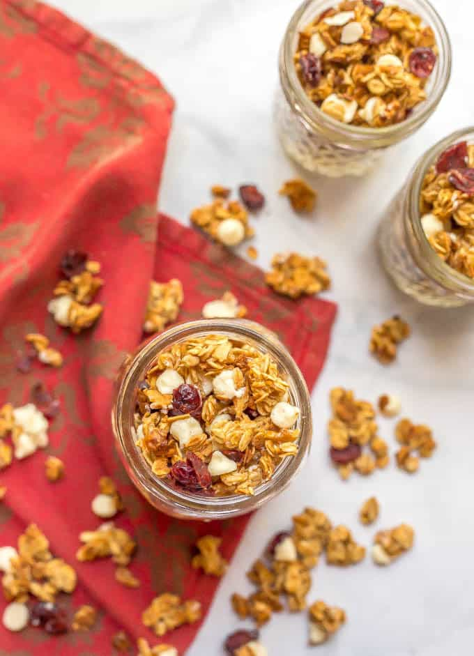 Cranberry white chocolate granola in glass jars with extra granola and red napkin scattered