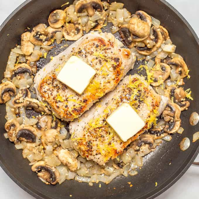 Overhead angle of Garlic butter pork chops with butter and lemon zest, in pan surrounded by onions and mushrooms