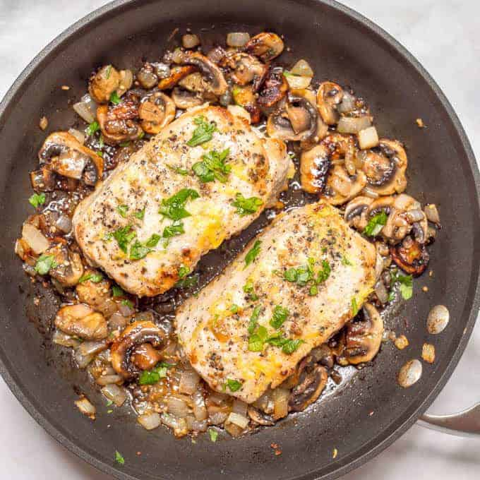 Overhead angle of garlic butter pork chops with parsley and lemon zest, in pan surrounded by onions and mushrooms