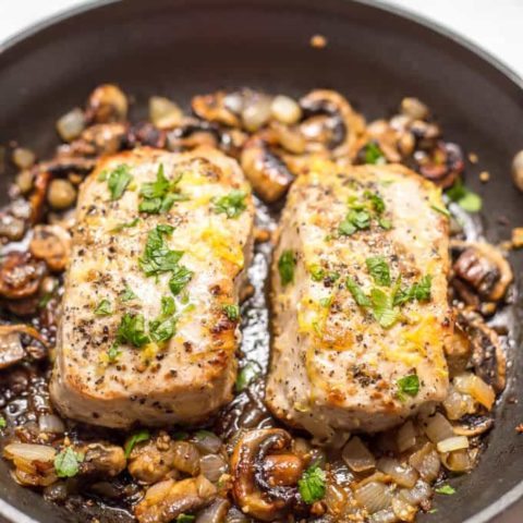 Garlic butter pork chops with parsley and lemon zest, in pan surrounded by onions and mushrooms