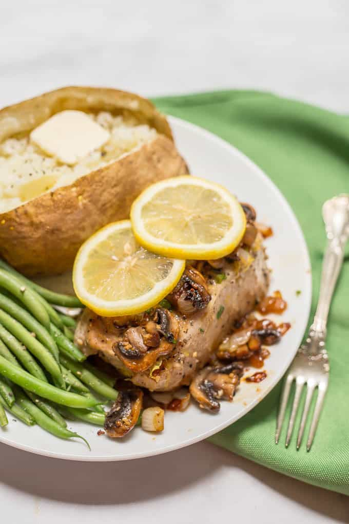 Garlic butter pork chops are an easy one-pan dish with a delicious mushroom-onion mixture and a hint of lemon to brighten all the flavors. Perfect for a weeknight family dinner! | www.familyfoodonthetable.com