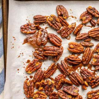 Close-up of sweet and spicy pecans on a baking sheet with parchment paper and a blue linen towel underneath the pan