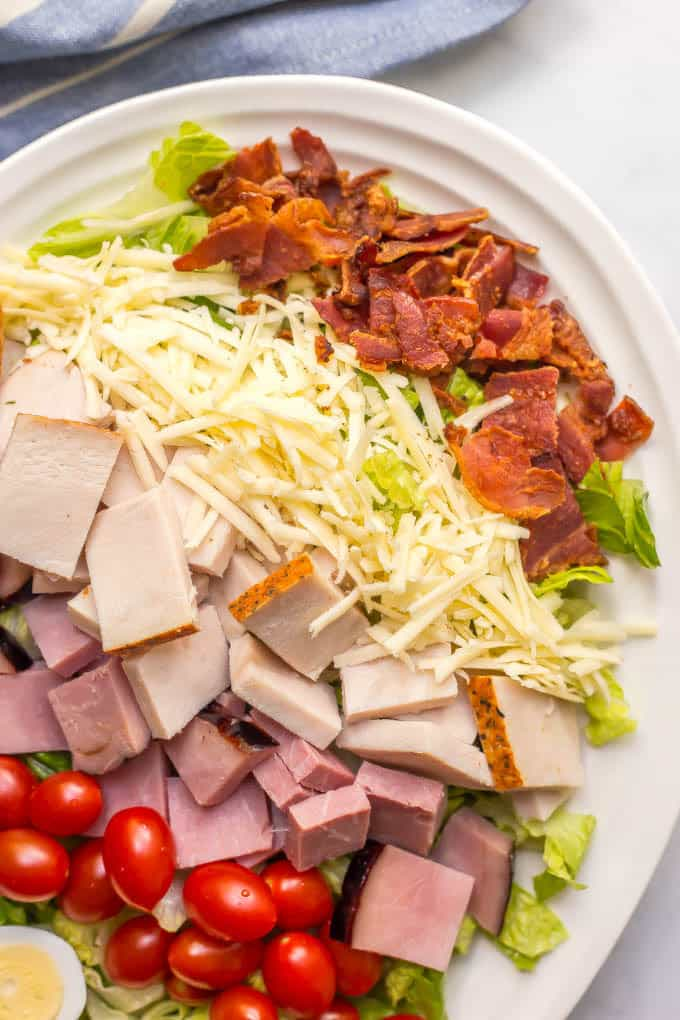 Close up of ingredients layered on a Thanksgiving chef salad in a white bowl: crumbled bacon, shredded cheese, turkey, ham and cherry tomatoes