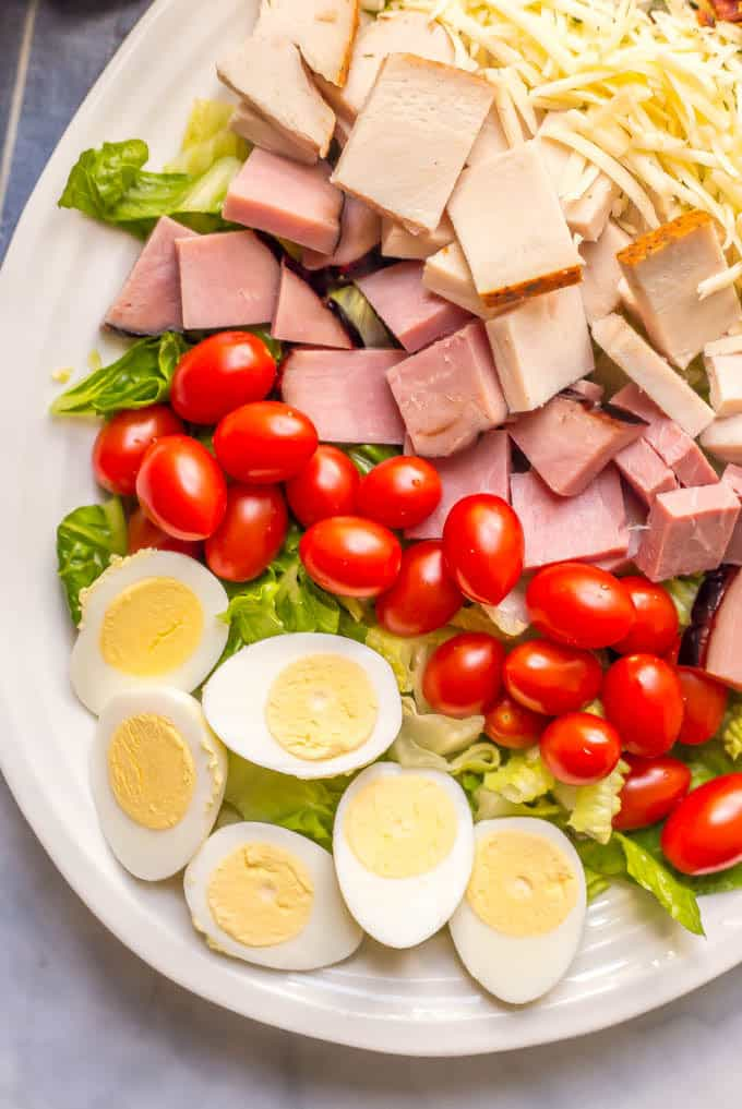 Close up of ingredients layered on a salad: hard boiled eggs, cherry tomatoes, ham, turkey and shredded cheese
